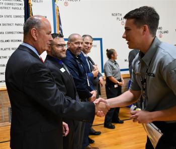 Peru State College Officer Intern Gabriel Stolinski shakes hands with Dir. Frakes upon receiving his certificate and badge